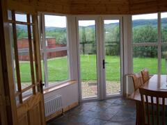Conservatory with table and chairs.  Magnificant Countryside views yet only yds from the Sea.