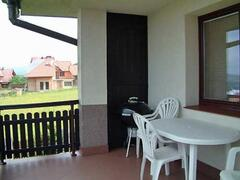 Wide balcony with seating and barbeque. Overlooks fields and countryside.