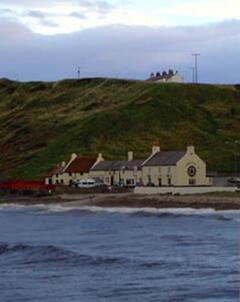 Property Photo: The cottage on the cliff top with The Ship Inn below.