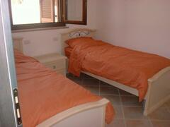 One of the spaciouse bedrooms with twin beds,wardrobe,air conditioning unit.