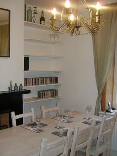 Elegant dining room with garden views, comfortably seating six, with original fireplace and stripped wood floors