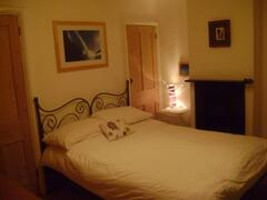 Double bedroom with original fireplace, valley and sea views