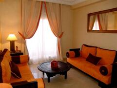 Spacious living room in orange & brown touch.