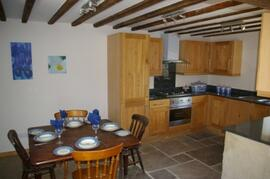 full granite and oak kitchen with dining area.