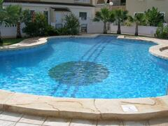 Property Photo: The private communal pool and garden area supports a fish shape children's pool and a guitar shape family pool