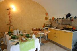 The kitchen Our fully furnished kitchen is colourful and cozy. The antique table reminds you of traditional tastes and invites you to long pleasant conversations among homemade cakes and fruit juices.