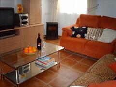 Apartment lounge contains two three-seater settees, coffee table and entertainment console.