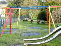 Large outside childrens play area with swings, slides, zip wire, basketball hoop, and in summern bouncy castle and trampolines