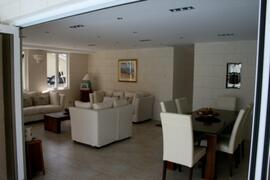 Living and dining area with seamless glass doors leading into pool area