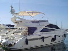 Property Photo: Picture showing flybridge with bimini and also full beam master cabin