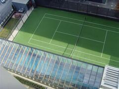 View of pool, BBQ & tennis court from balcony.