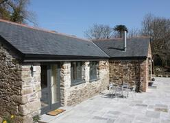 Property Photo: The front of the cottage showing patio area