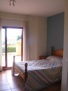 Main double bedroom with ensuite and terrace views of garden and pool