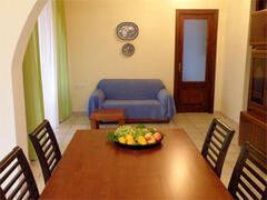 There is a large dining table centring the room, between seating area and kitchen.