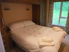 The master bedroom is located at the back of the lodge and has views towards the fells. There  are no lodges or footpaths located behind the lodge and therefore its a private secluded area.  Consisting of a double bed, ample storage options and LCD TV(freeview