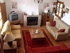 Lounge with air conditioning. Wifi is available within the villa. Fan assisted log fire, 3 sofas, red one goes into a double bed.  Free-view, and Spanish TV, DVD. Stereo. Games