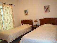 Twin bedroom with access to a balcony, in upper floor.