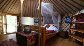Yurt Interior, queen bed, wood burner, shelving