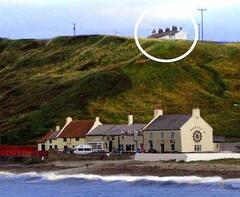 Property Photo: Cottage on cliff. Viewed from the pier.