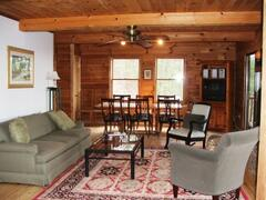 Spacious living/dining room with rock fireplace & open to deck